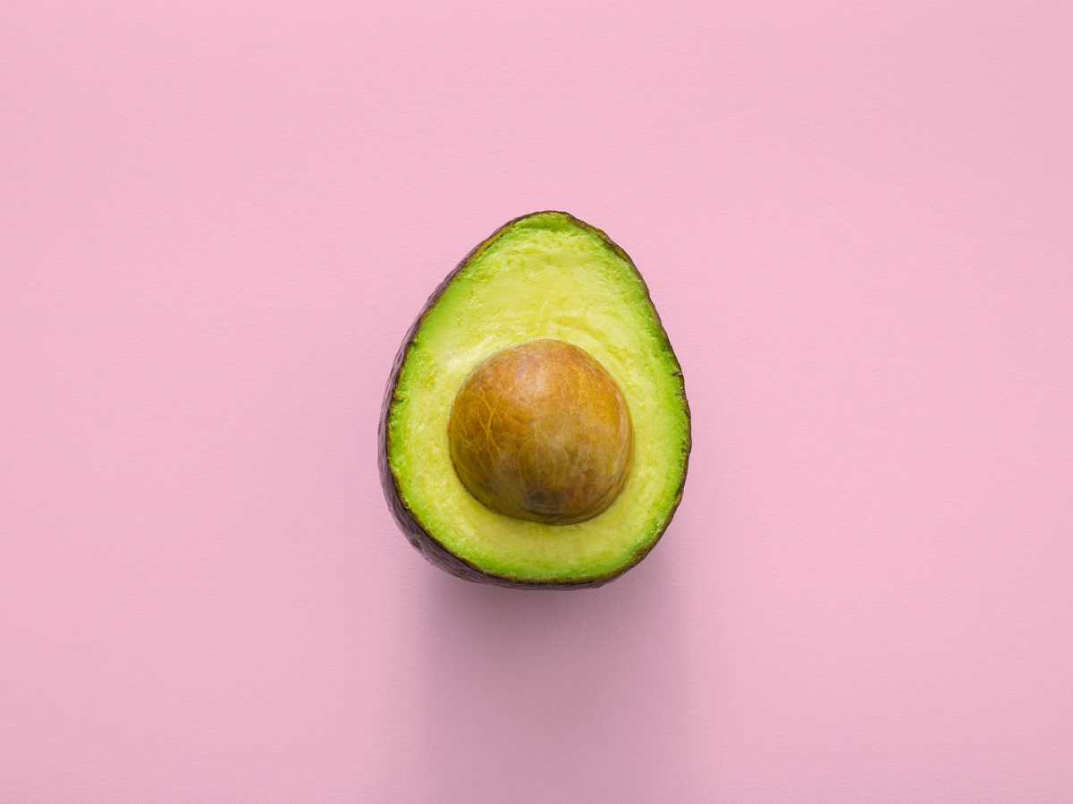 Avocado on a pink background - you can get many foods which provide protein and fat in a vegan diet