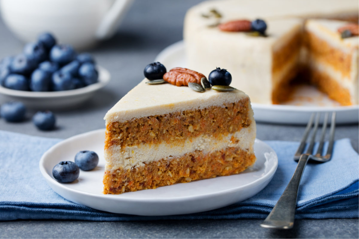 Vegan carrot cake on a table with a fork. Our vegan baking guide will help create tasty vegan bakes.
