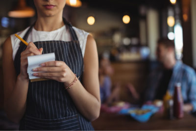 Unidentified waitress holding a notebook and pen to take someone's order