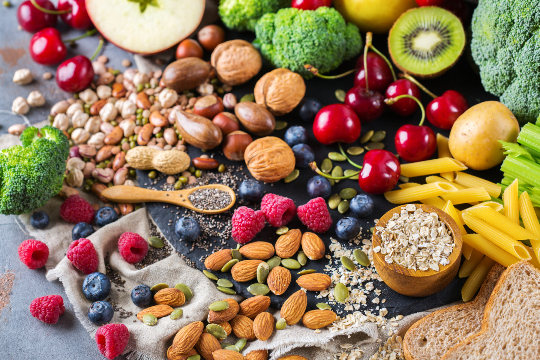 A selection of vegan food essentials, including nuts, fruits, vegetables and pulses. These items are common on a vegan shopping list.