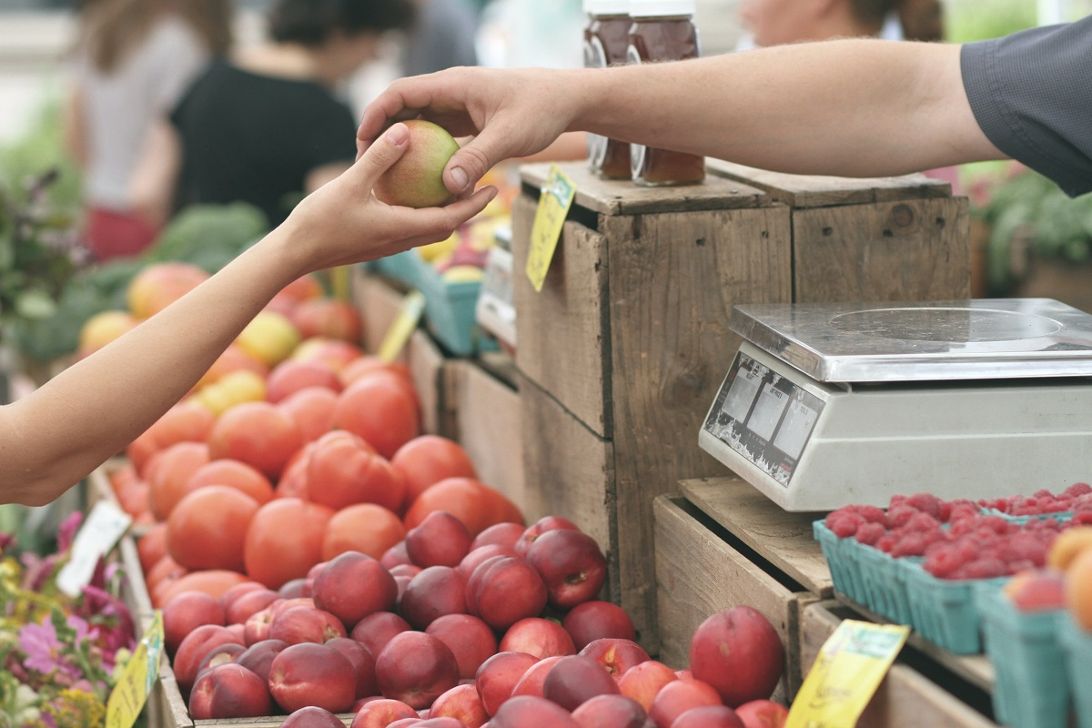 Unidentified person buying fruit from a local market
